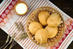 在柳条筐和牛奶杯子的新鲜的小圆面包在桌布 免版税库存图片