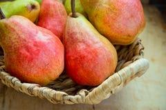 在柳条筐的五颜六色的成熟新鲜的有机梨在窗口附近的年迈的木厨房用桌上 库存图片