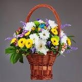 在柳条筐的五颜六色的花花束安排焦点 库存照片