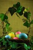 在柳条筐的复活节彩蛋与常春藤 免版税库存图片