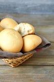 在柳条筐的小圆面包在木板 库存图片