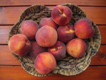 在柳条筐的成熟和水多的桃子在棕色木桌上 库存图片