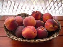在柳条筐的成熟和水多的桃子在游廊桌上 库存图片