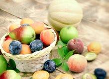 在柳条筐的新鲜的有机季节性果子在桌上 免版税库存图片
