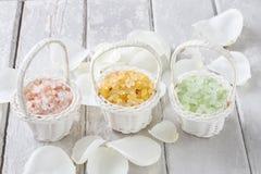 在柳条筐的海盐在白色玫瑰花瓣中 免版税库存照片