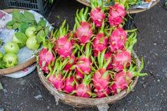 在柳条筐的龙果子在越南市场上 免版税库存图片