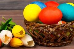 在柳条筐,红色和黄色郁金香的复活节彩蛋在木板 图库摄影