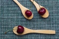 在柳条背景和三把木匙子,特写镜头的成熟樱桃 库存照片
