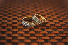 在柳条背景的两只金戒指 库存照片