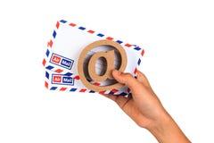 在标志和航空邮件信封在手边 图库摄影