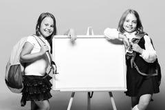 在标志板旁边的女小学生在蓝色背景 免版税图库摄影