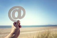 在标志的电子邮件在海滩夏天背景 库存照片