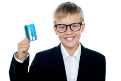 在标榜转账卡的西装的小孩 免版税库存照片