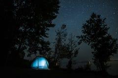 在树中的蓝色帐篷在海岸 图库摄影