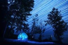 在树中的蓝色帐篷在海岸 库存照片