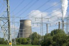 在树之间的能源厂和电定向塔 免版税库存照片