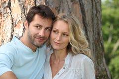 在树前面坐的夫妇 库存图片