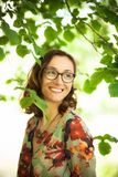 在树叶子之间的愉快的女孩 免版税图库摄影
