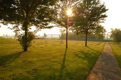 在树后的太阳其次在橄榄球场 免版税库存照片