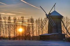 在树后的惊人的冬天日落在帐篷屋顶风车 库存照片