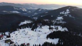 在树和雪盖的山的华美的空中射击用一个小村庄在最前面,4k 股票录像