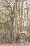 在树和鸟舍附近的老水井 免版税库存图片