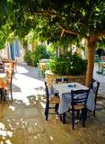 在树在村庄正方形的咖啡馆桌下, Vourliotes,萨莫斯岛, 免版税库存照片