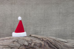 在树干的红色圣诞老人帽子圣诞节的- gre的木背景 库存照片