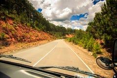 在树木繁茂的小山中的晴朗的高速公路在公共汽车窗口外面 免版税库存图片