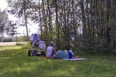 在树树荫下在新鲜空气休息的家庭的与str 库存图片