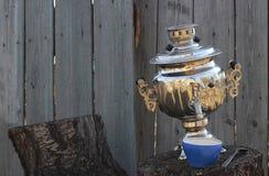 在树桩和杯子的老俄国式茶炊 免版税库存图片