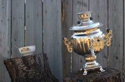 在树桩和碗的老俄国式茶炊 库存照片