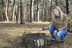 在树桩附近的森林女孩喂养与坚果的一只灰鼠 免版税库存图片