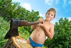 在树桩附近的轴男孩 图库摄影