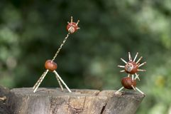 在树桩,绿色背景的两个滑稽的栗子动物,传统秋天手工造,狮子和长颈鹿 库存照片