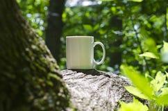 在树的一个独奏空白的加奶咖啡杯子 免版税库存照片