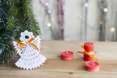 在树的圣诞节天使和在五颜六色的背景bokeh的红色蜡烛在圣诞节和新年装饰中 免版税图库摄影