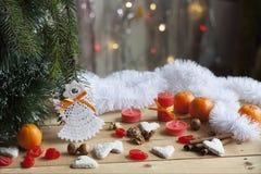在树的圣诞节天使和在五颜六色的背景bokeh的红色蜡烛在圣诞节和新年装饰中 免版税库存图片