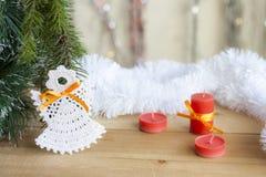 在树的圣诞节天使和在五颜六色的背景bokeh的红色蜡烛在圣诞节和新年装饰中 库存照片