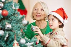 在树的男孩和祖母垂悬的圣诞树球 免版税库存图片