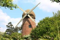 在树的老风车 免版税库存图片