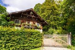 在树篱后的木瑞士山中的牧人小屋样式家 免版税图库摄影