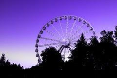 在树背景中弗累斯大转轮游乐园与年18-3838的一种明亮的日落光现代颜色的 库存照片
