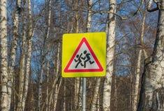 在树背景,俄罗斯的黄色学校路标 仔细孩子 免版税库存图片