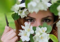 在树花后的女孩眼睛 图库摄影