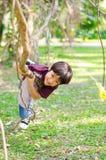 在树长袍的小男孩攀登 免版税库存照片