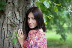 在树附近的一个少妇在夏天 免版税库存图片