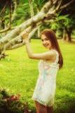 在树附近的亚洲美好的女孩立场在公园 免版税库存照片