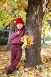 在树附近的女孩立场在秋天森林,黄色在背景离开 库存图片