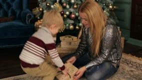在树附近的妈妈和儿子开放圣诞节礼物 股票录像